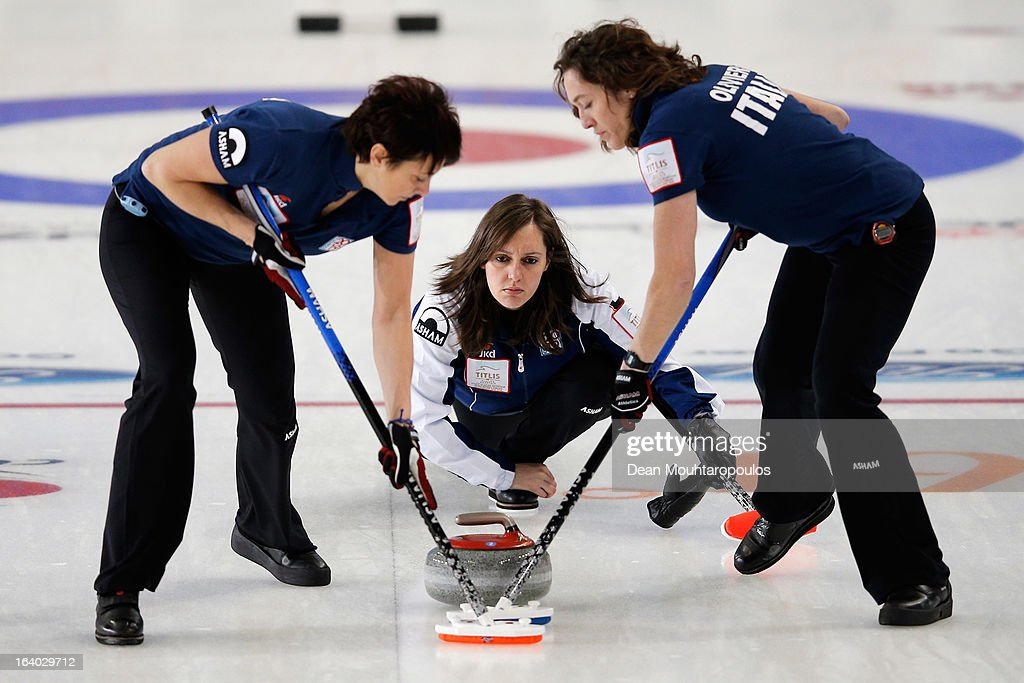 Diana Gaspari (C) of Italy looks on after throwning the stone as Chiara Olivieri (R) and Claudia Alvera (L) sweep in the match between Japan and Italy on Day 4 of the Titlis Glacier Mountain World Women's Curling Championship at the Volvo Sports Centre on March 19, 2013 in Riga, Latvia.