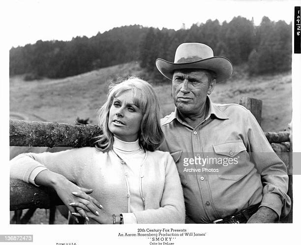 Diana Hyland and unidentified man leaning against ranch post in a scene from the film 'Smoky', 1966.