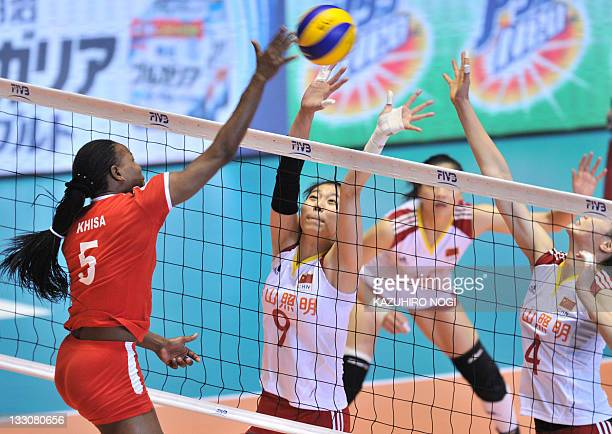 Diana Khisa of Kenya attacks over Chinese players Yang Junjing and Hui Ruoqi during a match of the World Cup women's volleyball tournament in Tokyo...