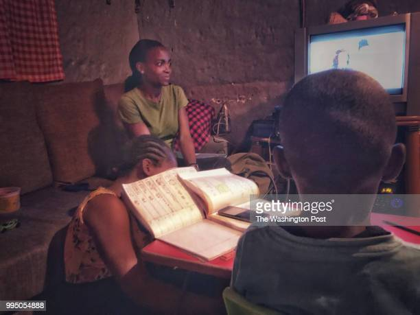 Diana Kuya watches a soap opera before dinner in her family's threeroom home in Nairobi Kenya Her niece Natalia Marsha hides from the camera under...