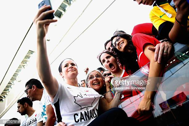 Diana Matheson of Canada celebrates with supporters with her medal following her teams victory during the Women's Olympic Football Bronze Medal match...