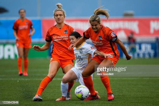 Diana Matheson of Utah Royals FC drives between Kristie Mewis and Kathrine Stengel of Houston Dash during a game in the first round of the NWSL...