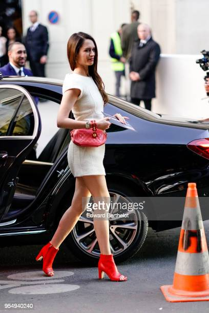 Diana Pozharskaya wears a white dress a pink Chanel bag red leather shoes outside the Chanel Cruise 2018/2019 Collection at Le Grand Palais on May 03...