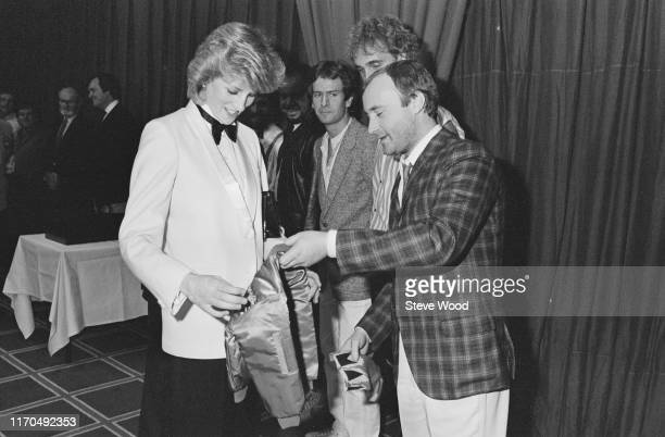 Diana Princess of Wales accepts a jacket with an embroidered gold crown for Prince William from British singer and drummer Phil Collins of rock band...