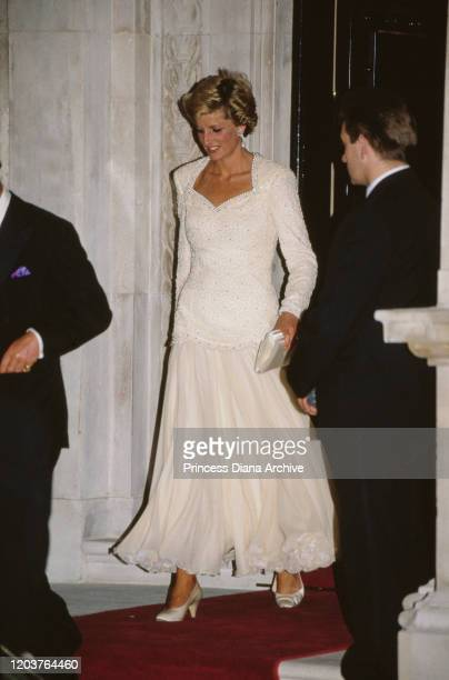 Diana, Princess of Wales arrives at a party held for the former King Constantine of Greece in London, June 1989. She is wearing a white beaded dress...
