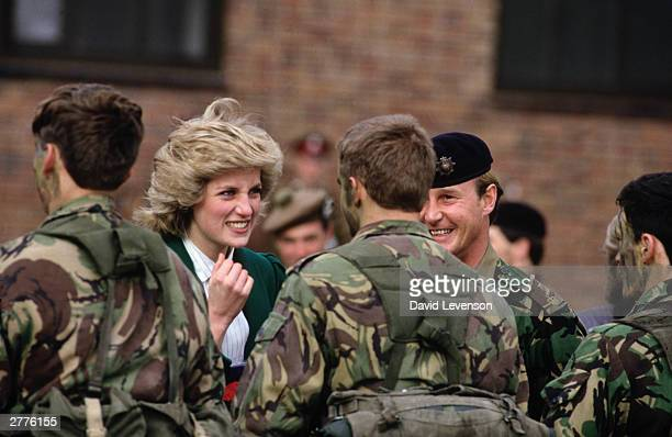 Diana Princess of Wales as ColonelinChief of the Royal Hampshire Regiment jokes with a soldier about his camouflage face paint at an army base on...