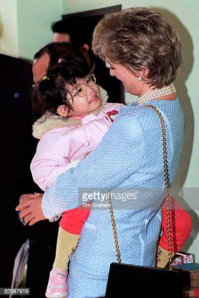 Diana Princess Of Wales At The Umeda Akebone School In Tokyo Japan The Princess Is Holding A Little Japanese Girl In Her Arms They Are Smiling At...