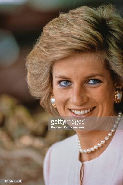 Diana, Princess of Wales attends a camel race at Al Maqam, near Al Ain in Abu Dhabi in the United Arab Emirates, March 1989. She is wearing a pale...