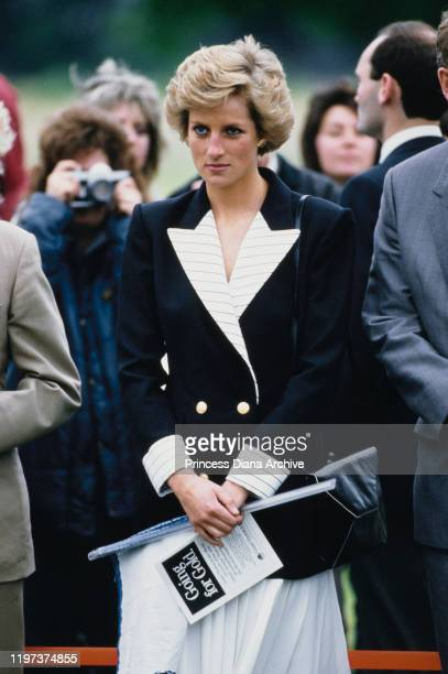Diana, Princess of Wales attends the start of a Pentathlon in Windsor Great Park, England, 10th July 1988. She is wearing a black and white suit by...