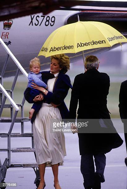 Diana Princess of Wales carries a baby Prince Harry from the Queens Flight aircraft on arrival on September 23 1985 at Aberdeen airport in Scotland...