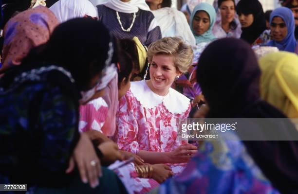 Diana Princess of Wales chats to female students during a visit to Oman University in November during the Royal Tour of Oman Diana wore a dress...