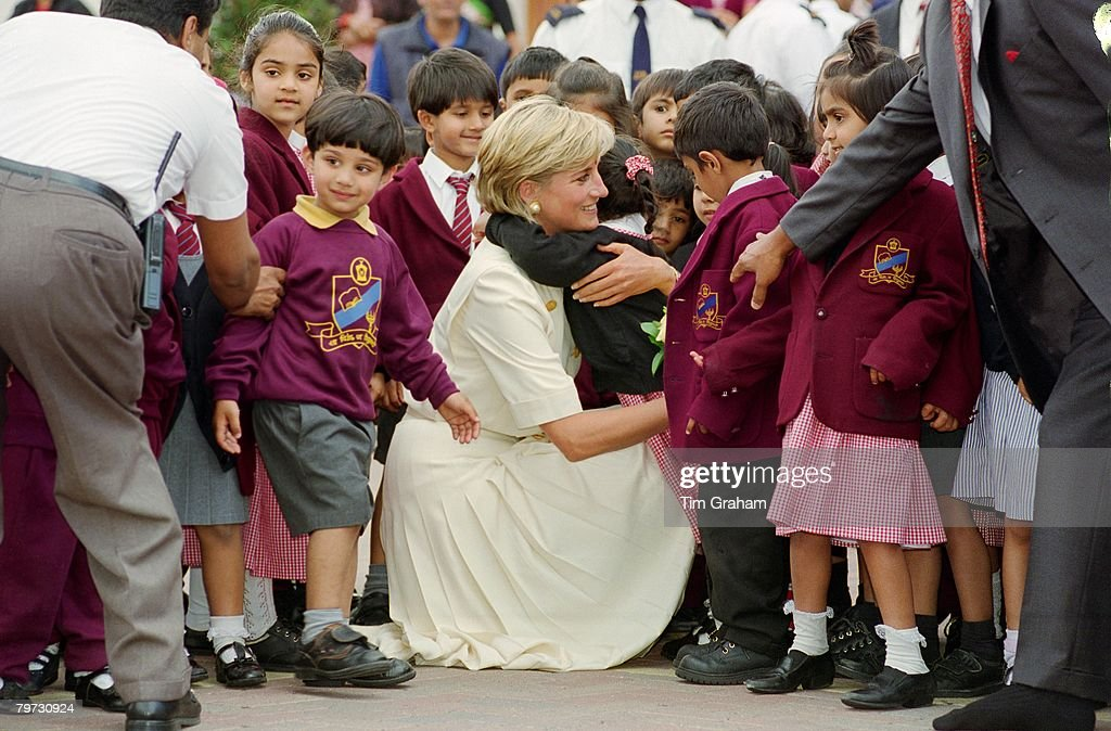 Diana, Princess of Wales crouching down to embrace a pupil a : News Photo