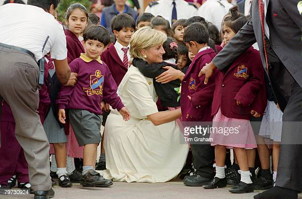 Diana Princess of Wales crouching down to embrace a pupil at the Shri Swaminarayan Mandir in Neasden