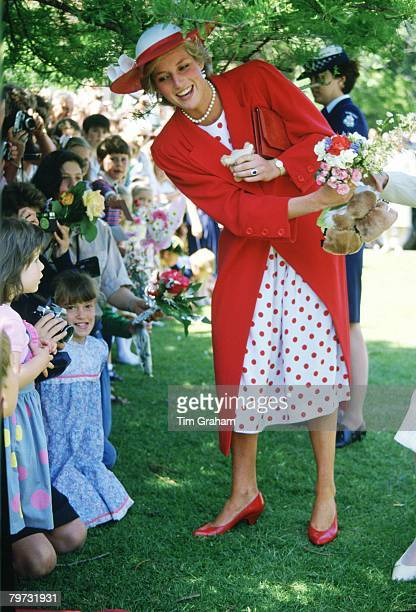 Diana, Princess of Wales hands the flowers she receives from well-wishers to an aid during a visit to the Royal Botanical Gardens in Melbourne,...