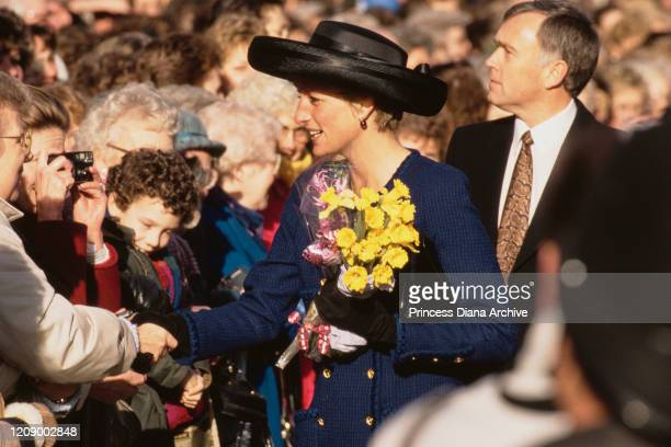 Diana Princess of Wales holding a bunch of daffodils during a visit to Peterborough UK January 1991 She is wearing a blue suit by Chanel and a black...