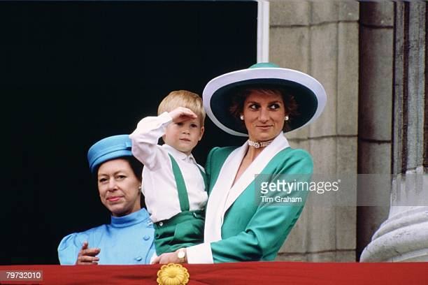 Diana Princess of Wales holding a young Prince Harry in her arms as she watches Trooping the Colour with Princess Margaret from the balcony of...