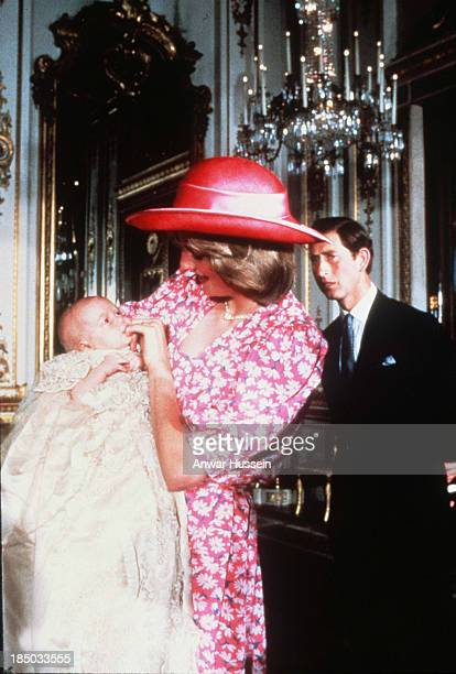 Diana Princess of Wales holds baby Prince William as Prince Charles Prince of Wales looks on at William's christening in the music room at Buckingham...