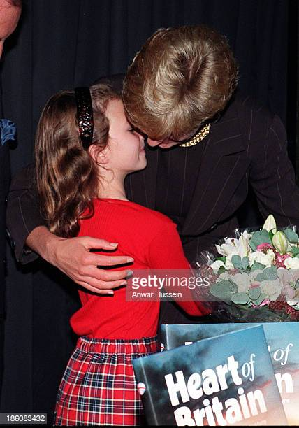 Diana Princess of Wales hugs Danielle Stephenson a young child whose life was saved by pioneering surgeons at Harrods book department where she was...
