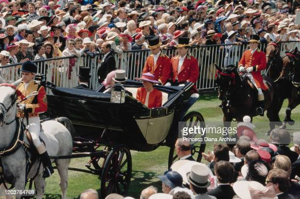Diana Princess of Wales in a carriage with the Queen Mother on the first day of the Royal Ascot race meeting UK June 1990 Diana is wearing a red and...