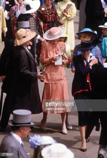 Diana Princess of Wales is bumped into by a woman crossing the Royal Enclosure during Royal Ascot races on June 20 1985 at Ascot Berkshire Diana wore...