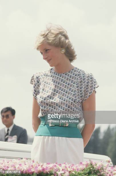 Diana, Princess of Wales is taken on a river cruise past the Grand Palace in Bangkok, Thailand, February 1988. She is wearing a dress by Alistair...