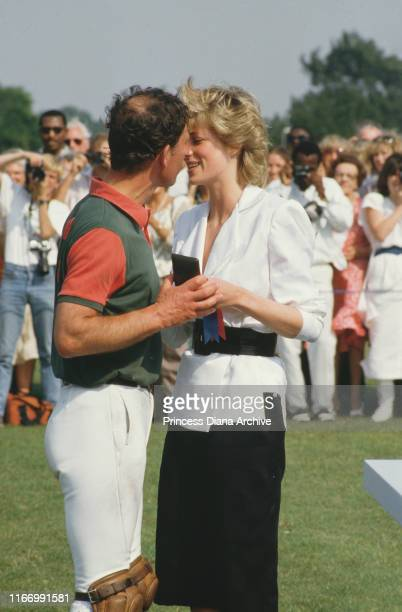 Diana, Princess of Wales kissing Prince Charles on Smith's Lawn of the Guards Polo Club in Windsor, UK, July 1986. Charles is dressed in polo gear.