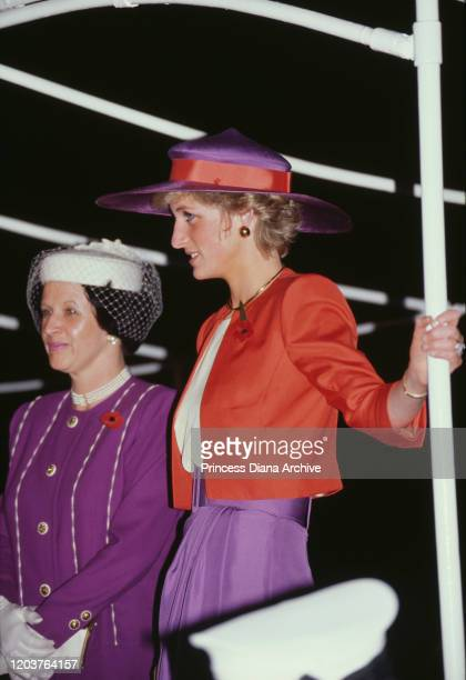 Diana Princess of Wales on the Governor's launch in Hong Kong November 1989 She is wearing a red and purple suit by Catherine Walker and a poppy