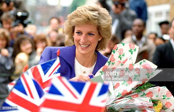 Diana Princess Of Wales Patron Of The Guinness Trust Being Presented With Flowers By The Crowd Gathered To Greet Her With Union Jack Flags Outside...