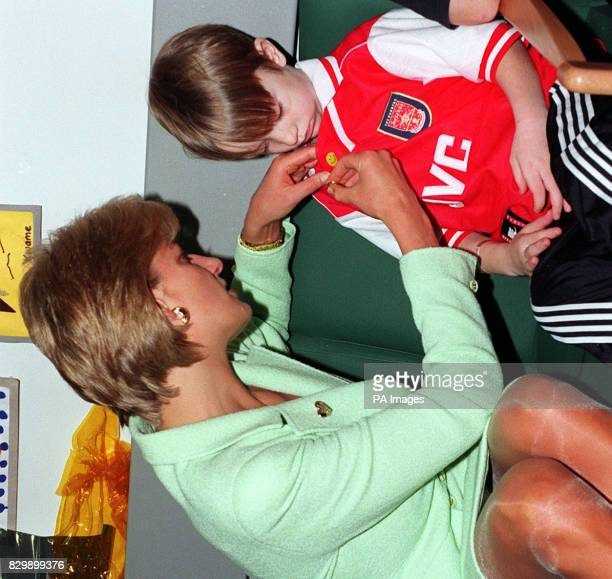 Diana Princess of Wales pins a Variety Club gold heart on 7yearold Luke Stevens during her visit to Great Ormond Street Hospital on Gold Heart Day...