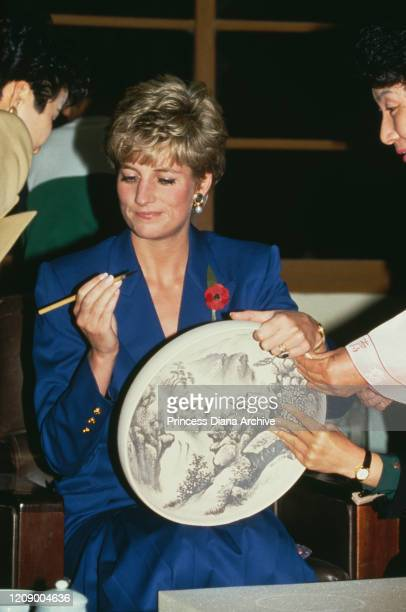 Diana, Princess of Wales signs a bowl for pupils at a school for deaf and dumb children in Ulsan, South Korea, 5th November 1992.