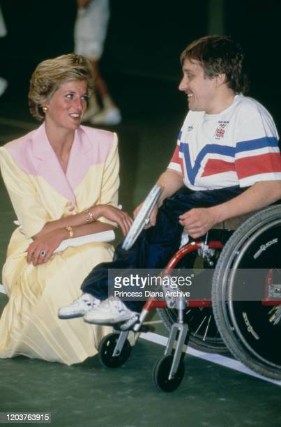 Diana Princess of Wales talks to a tennis player in a wheelchair at a sports centre in Nottingham UK May 1990 She is wearing a suit by Catherine...