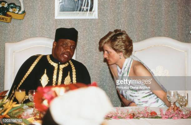 Diana, Princess of Wales talks to Nigerian President Ibrahim Babangida during a presidential banquet in Lagos, Nigeria, March 1990. She is wearing an...
