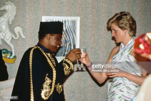 Diana, Princess of Wales toasts Nigerian President Ibrahim Babangida during a presidential banquet in Lagos, Nigeria, March 1990. She is wearing an...