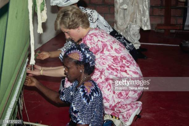 Diana Princess of Wales tries weaving on a loom in Umuagbai village Nigeria March 1990 She is wearing a patterned dress by Paul Costelloe