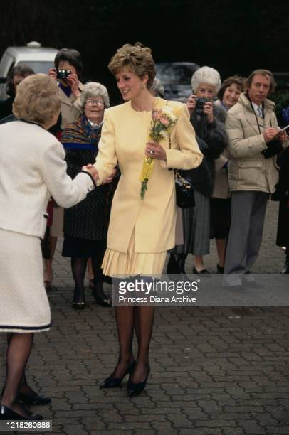 Diana, Princess of Wales visits a hospice in Windsor, UK, 27th January 1992. She is wearing a pale yellow suit by Catherine Walker and a Chanel...