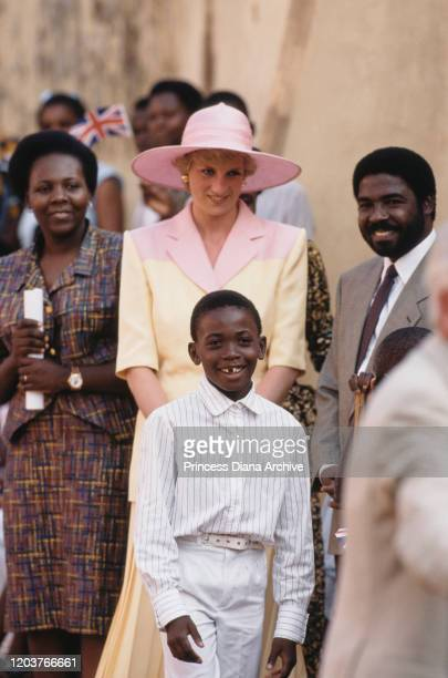 Diana, Princess of Wales visits a school for the deaf and dumb in Yaoundé, Cameroon, March 1990. She is wearing a pink and yellow suit by Catherine...