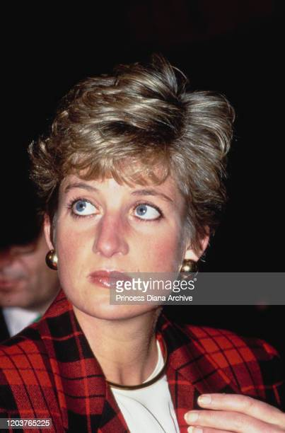 Diana Princess of Wales visits an Italiana exhibition at the Orangery in Kensington Palace London December 1990 She is wearing a red and black suit...