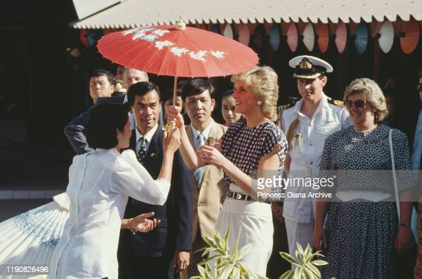 Diana, Princess of Wales visits an umbrella factory in Chiang Mai, Thailand, February 1988. She is wearing a dress by Alistair Blair. On the right is...