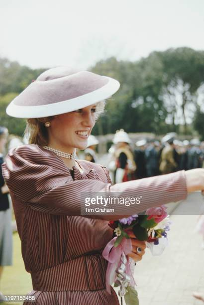 Diana, Princess of Wales visits the Commonwealth War Cemetery in Anzio, Italy, April 1985. She is wearing a striped dress and a hat by Frederick Fox.
