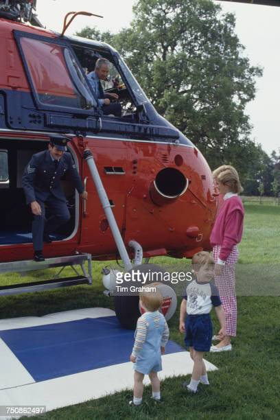 Diana Princess of Wales watches as Prince William and Prince Harry prepare to board a helicopter of the Royal Flight for a brief flight over...