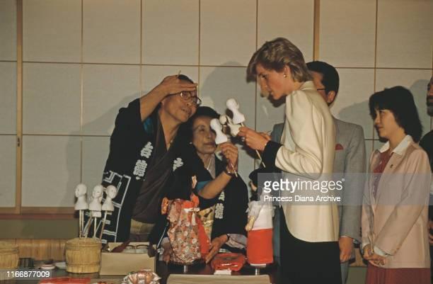 Diana, Princess of Wales watching a craftsman making traditional Japanese dolls at the Akasaka Palace in Tokyo, Japan, May 1986. Diana is wearing a...