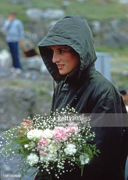 Diana, Princess of Wales, wearing a Barbour waxed jacket with the hood up, holds a bouquet during a visit to Barra on July 3, 1985 in the Western...