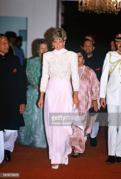Diana, Princess of Wales, wearing a beaded evening gown with a pink chiffon sarong style detail designed by Catherine Walker, attends a dinner hosted...