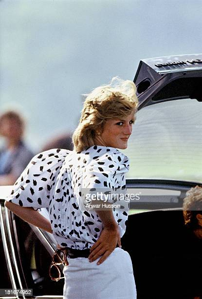 Diana, Princess of Wales, wearing a black and white patterned blouse and a white pencil skirt, stands with her hands on her hips during a polo match...