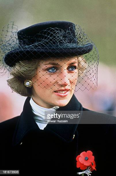 Diana, Princess of Wales, wearing a black coat with gold buttons designed by Jasper Conran, a black hat with netting designed by Viv Knowland and a...