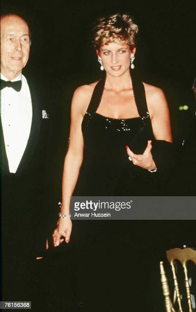 Diana, Princess of Wales, wearing a black halter-neck evening gown with bugle beads designed by Catherine Walker, stands next to French President,...