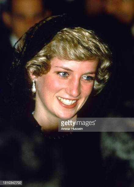 Diana, Princess of Wales, wearing a black lace dress designed by Catherine Walker and a mantilla veil to cover her hair, smiles as she visits The...