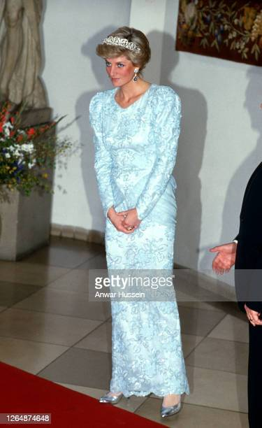 Diana, Princess of Wales, wearing a blue chiffon and lace dress with sequins designed by Catherine Walker, the leaf and flower diamond Spencer family...