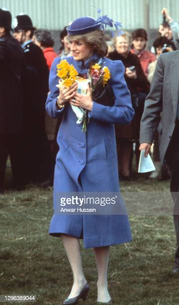 Diana, Princess of Wales, wearing a blue coat with puffed sleeves and a blue velvet hat with feathery silk fronds, is seen during a visit to the...