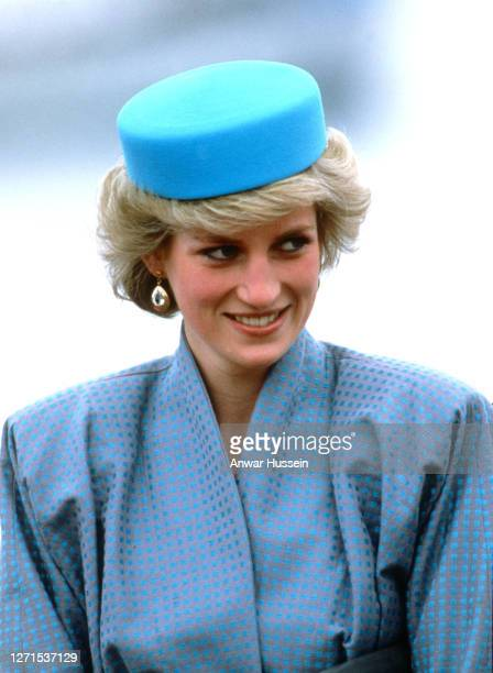 Diana, Princess of Wales, wearing a blue pillbox hat designed by milliner Gina Foster, smiles as she attends a reception at Swy-A-Lane Park on May 1,...